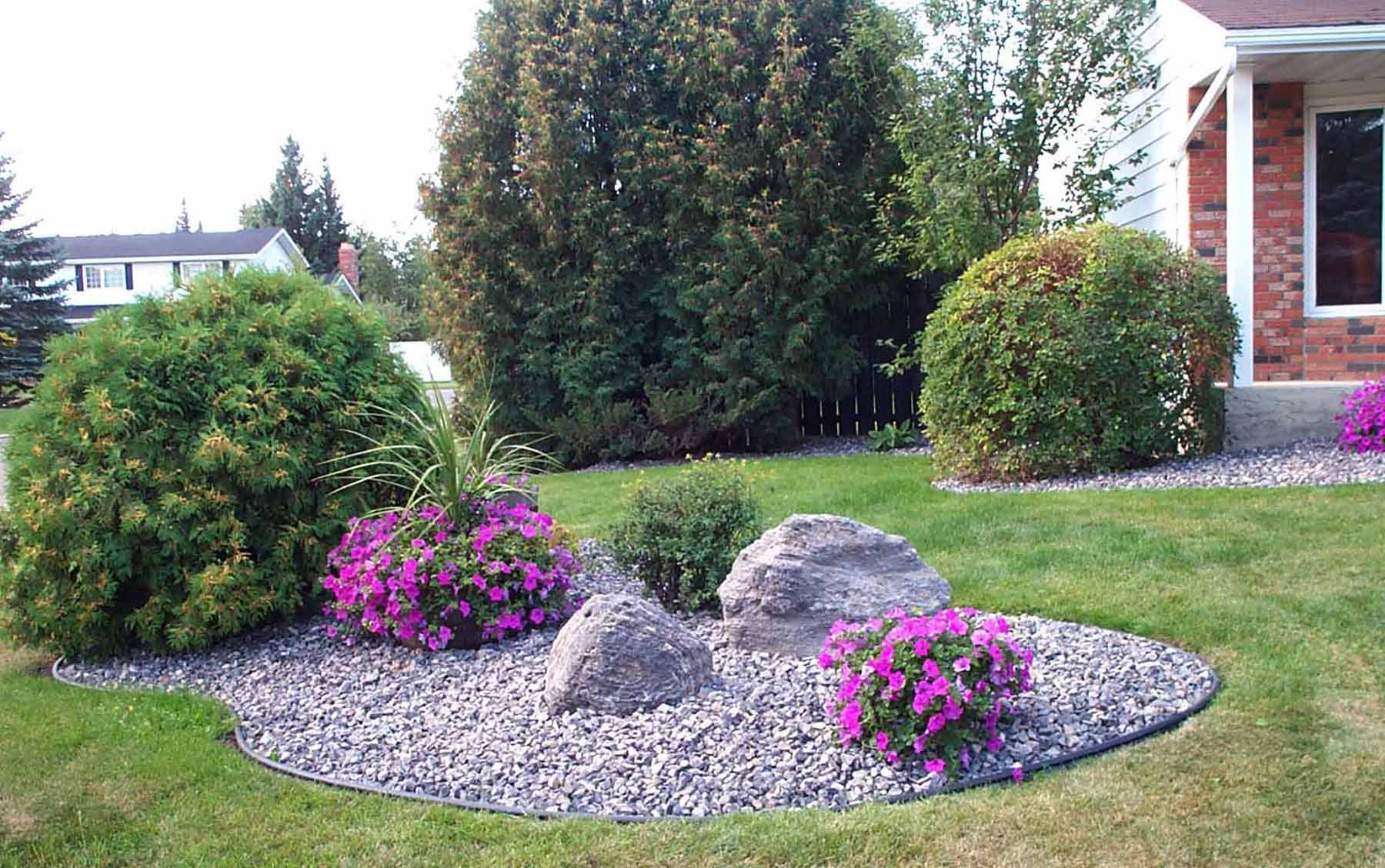 Grey boulders and gravel in flower bed