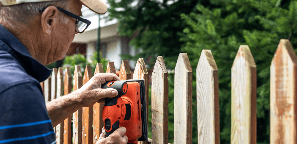 man working on fence with sander